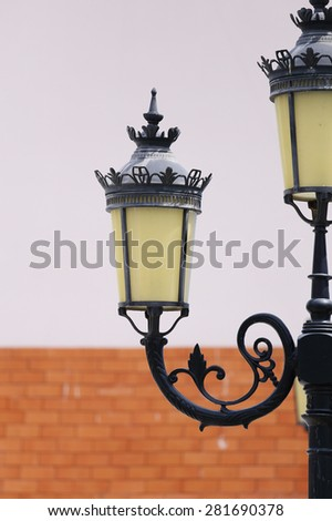 Antique lamp post with a wall background - stock photo