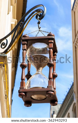 Antique large hourglass hanging in old town on blue sky background. Multicolored vibrant outdoors vertical image.