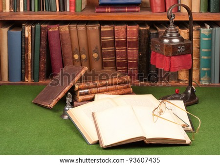Antique leather books, lamp and reading glasses on green blotter. - stock photo