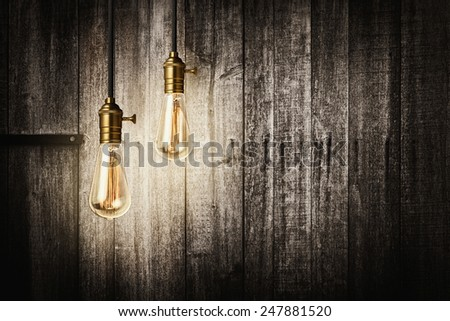 Antique light bulbs on wooden background - stock photo