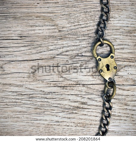 Antique lock and chain on wood - stock photo
