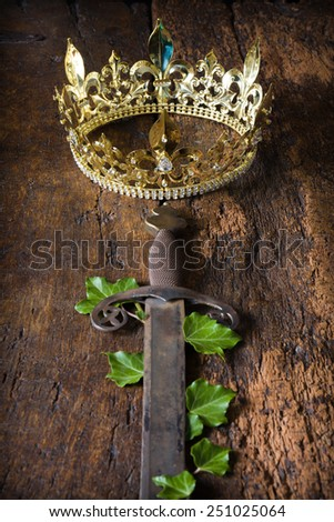 Antique medieval sword and golden crown decorated with ivy - stock photo