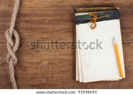 Antique Notebook (1940th, Original) on the wood with rope knot background - stock photo