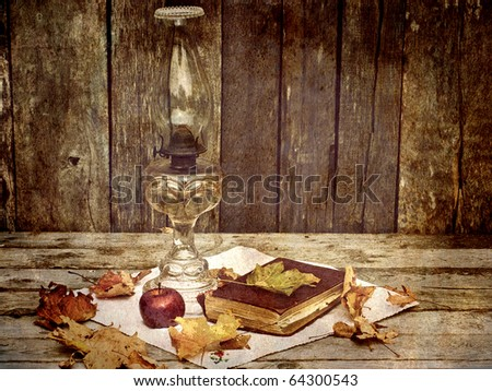 Antique oil lamp, a fresh apple, autumn leaves and an old book on an antique cloth on a grunge wood background.  Grunge textured. - stock photo