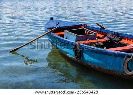 Antique, old wooden fishing boat with oars on lake in Chile - stock photo