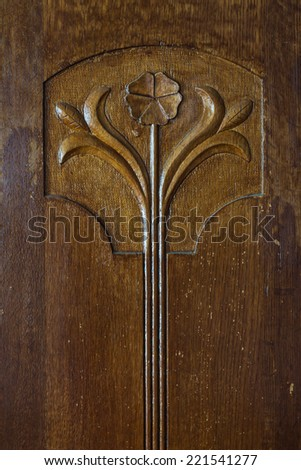 Antique ornament with flower in modern style on an old oak-tree cabinet door. Luxury wooden furniture with natural wood