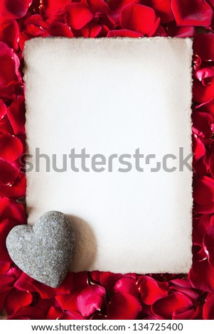 antique paper with a stone heart framed from red rose petals