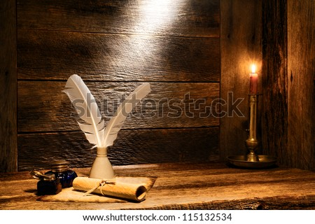 Antique parchment paper sheets roll with old writing feather quills in vintage ink well and ancient colonial blue glass inkwells on distressed ancient wood desk by candlelight in ancient historic home - stock photo