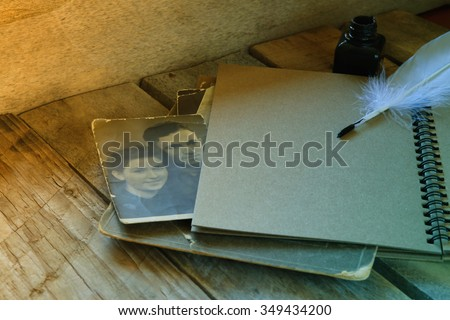 antique photos and old open notebook on wooden table. retro toned and filtered image. selective focus - stock photo