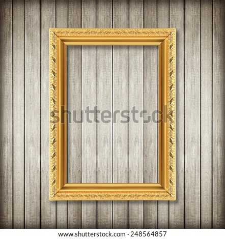 Antique picture frame on wooden wall ;. Empty picture frame on wooden wall.