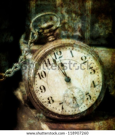 Antique pocket clock showing a few minutes to midnight grungy style. Concept of time,the past. - stock photo