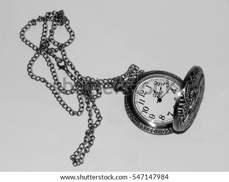 Antique pocket watch on a black and white photo