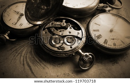 Antique pocket watch on old photos back, sepia - stock photo