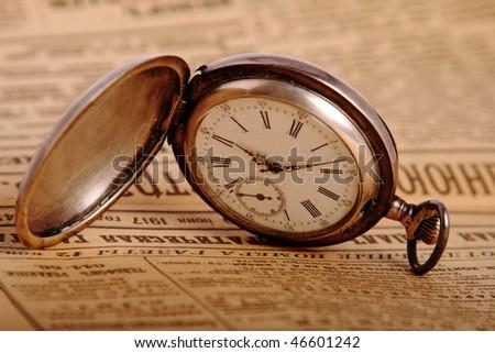 Antique pocket watch on vintage newspaper - stock photo