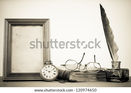 Antique pocket watch, quill and inkwell, photo frame, book, specs on wooden table - stock photo