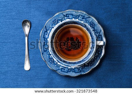 antique porcelain blue and white tea cup on blue background