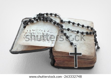 Antique prayer-book and a black rosary on it in a white background.This is not a text but meaningless signs created by the photographer. - stock photo