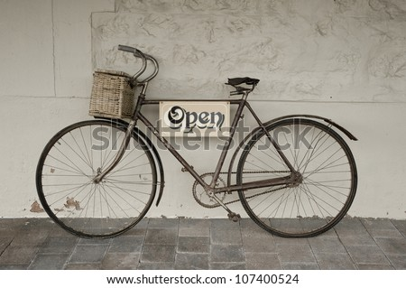 Antique push bike used for an open sign for an Antique shop. - stock photo