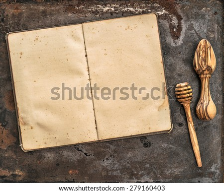Antique recipe book and wooden kitchen utensils. Retro style toned picture.