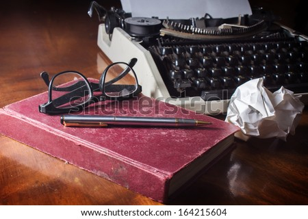Antique red book and pen, glasses with old typewriter. - stock photo