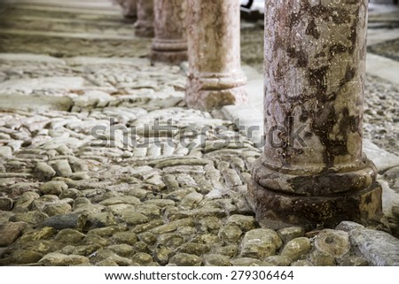 antique red marble columns resting on stone floor - stock photo