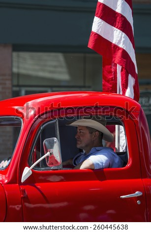 Antique Red Truck and cowboy drive in July 4, Independence Day Parade, Telluride, Colorado, USA, 04.07.2014 - stock photo