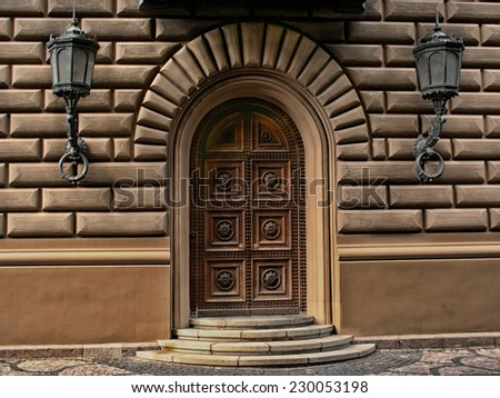 Antique, rich ornate door between two lanterns. - stock photo