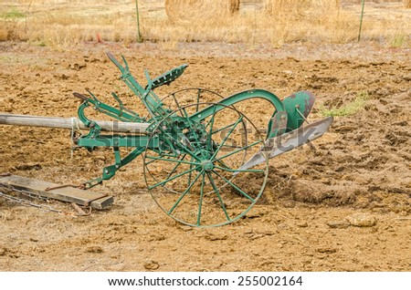 Antique riding plow for plowing a garden is drawn by a team of two horses - stock photo