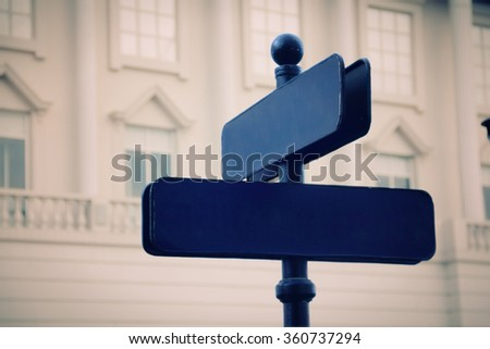 Antique road sign outside a building, in vintage color - stock photo