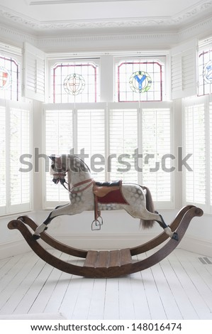 Antique rocking horse in bay window with stained glass - stock photo