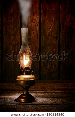 Antique rustic kerosene oil lantern lamp burning light with a soft glow flame making smoke on a vintage wood table in an old western ranch barn  - stock photo