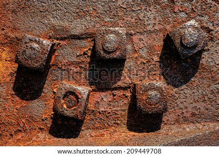 Antique rusty metal square nuts locked with rust and corrosion on old heavy duty bolts holding a thick and corroded vintage industrial steel plate structure as a retro grunge background - stock photo