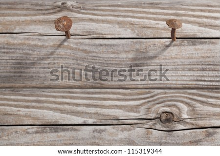 Antique rusty nail embedded in a of wood. Focus is on the head of the nail.