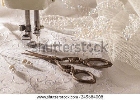 Antique sewing scissors and bridal material with sewing machine - stock photo