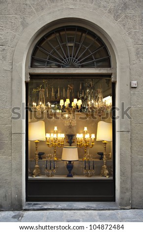 Antique shop windows full of lamps in traditional Italian shopping center in old town of Florence. Useful file for your brochure, flyer and site related to antiques store and fine-art auctions. - stock photo