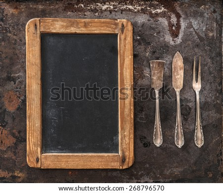 Antique silver cutlery and blackboard for your text. Retro style toned picture - stock photo