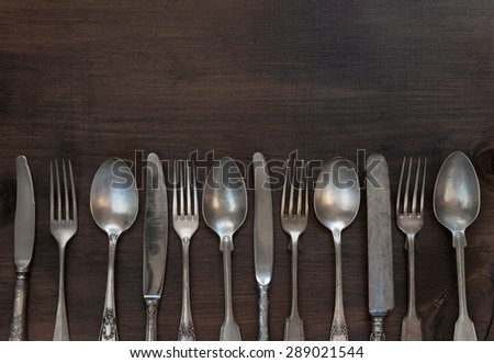 Antique silver cutlery in a row on old wooden background - stock photo