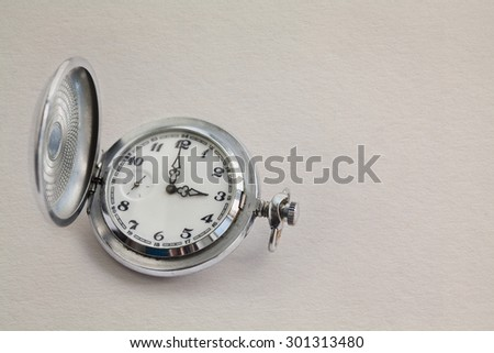 Antique silver, metal pocket watch showing a three o'clock. on vintage white paper background texture. Classic time concept. Macro view clock face. Copy space. - stock photo