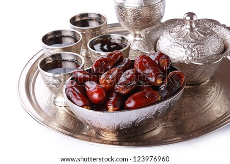 Antique silver pitcher and coffee cup set with dates in a tray isolated on a white background