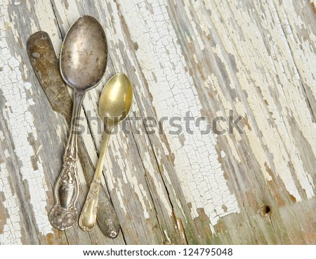 Antique silver spoons and a butter knife on a weathered plank surface - stock photo