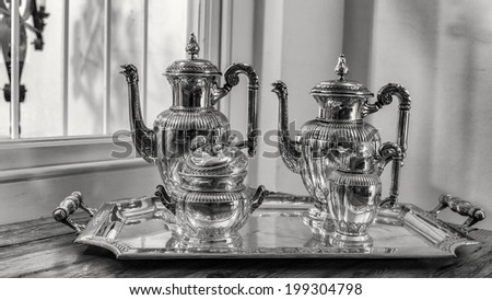 antique silver tea set with a two teapots, milk jug, sugar bowl, and a tray - stock photo