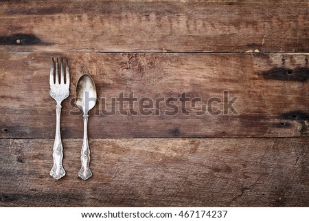 Antique silverware spoon and fork over a rustic old wooden background. Image shot from overhead.