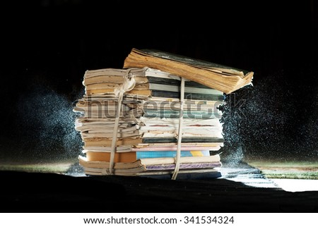 antique stack of books and notebooks with an expanding dust - stock photo