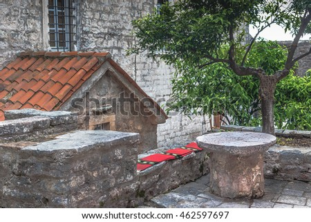 Antique stone patio. Stone table . Stone bench . Bright cover on the bench . Stone elucidated . Antique interior .