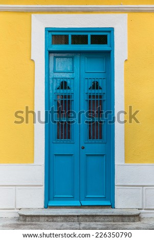 Antique style blue door on yellow wall