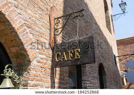 antique style cafe sign board with old architecture - stock photo