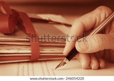 Antique style Vintage Hand writing letter with fountain pen next to mail tied with ribbon Closeup  - stock photo
