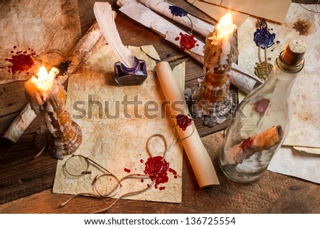 Antique table filled with old papers, red sealant and candles - stock photo