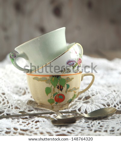 Antique tea cups and spoons - stock photo