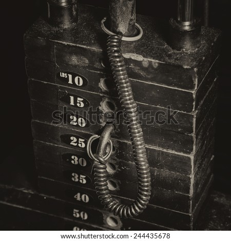 Antique tones on an old rusty weight stack in a gym. - stock photo